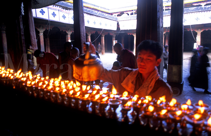 Monk pouring Yak wax into candles at the Jokhang temple in capital city of Lhasa Tibet China