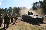 "German soldiers with the 295th Artillery Battalion stand around beside a German tank in the Drawsko Pomorskie Training Area in Poland on June 10, 2015.  NATO is engaged in a multilateral training exercise ""Saber Strike,"" the first time Poland has hosted such war games, involving the militaries of Canada, Denmark, Germany, Poland, and the United States."