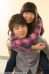 Education high school couple posing in corridor, girl getting piggy back ride from boyfriend