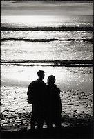 Sihlouetted couple embracing and looking out to sea at Sunset<br />