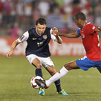 USMNT defender Michael Parkhurst (15) attempts to control the ball as Costa Rican defender Junior Diaz (15) defends. In CONCACAF Gold Cup Group Stage, the U.S. Men's National Team (USMNT) (blue/white) defeated Costa Rica (red/blue), 1-0, at Rentschler Field, East Hartford, CT on July 16, 2013.