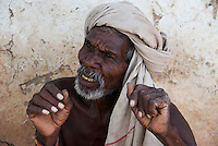A tribal Indian man with raised hands in gesture, near Gwalior, India.