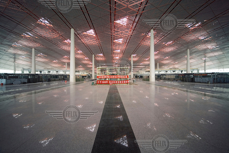 A motivational slogan encouraging worker efficiency, safety and quality (throughout the 100-day short-term target) inside Beijing's new airport. The airport, which is still under construction, was designed by Norman Foster.
