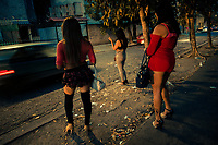 Salvadoran transgender sex workers stand by the roadside while waiting for clients in cars during the dusk in San Salvador, El Salvador, 7 April 2018. Although prostitution is not legal in El Salvador, dozens of street sex workers, wearing provocative miniskirts, hang out in the dirty streets close to the capital's historic center. Sex workers of all ages are seen on the streets but a significant part of them are single mothers abandoned by their male partners. Due to the absence of state social programs, they often seek solutions to their economic problems in sex work. The environment of street sex business is strongly competitive and dangerous, closely tied to the criminal networks (street gangs) that demand extortion payments. Therefore, sex workers employ any tool at their disposal to struggle hard, either with their fellow workers, with violent clients or with gang members who operate in the harsh world of street prostitution.