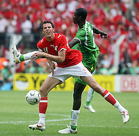 Switzerland's Marco Streller (11) and Togo's Dare Nibombe (right) colide. Switzerland defeated Togo 2-0 in their FIFA World Cup Group G match in Dortmund, Germany, June 19, 2006.