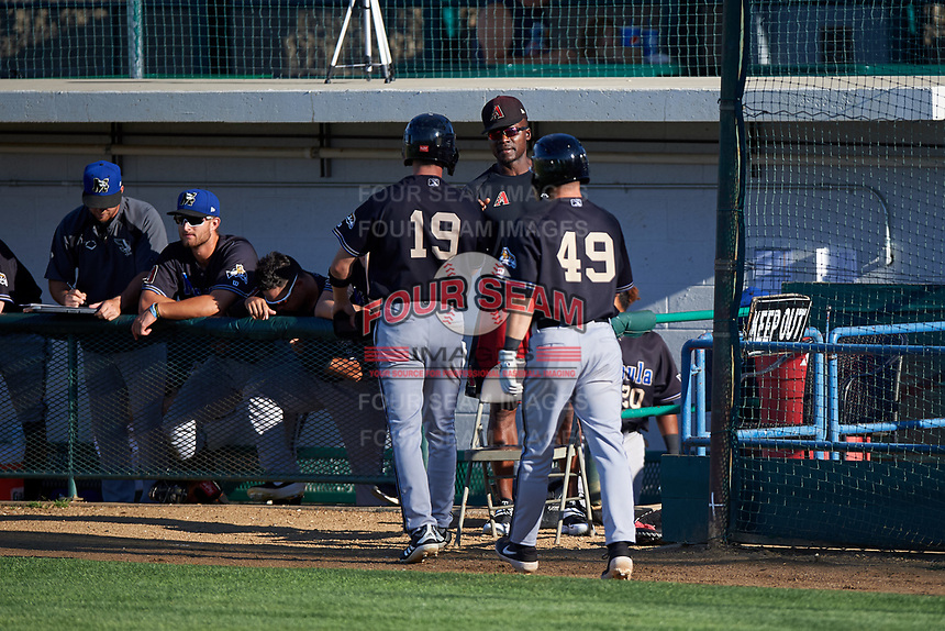 Missoula Osprey Kevin Watson Jr. (19) and Nick Grande (49) are congratulated by Orlando Hudson after Grande's home run during a Pioneer League game against the Great Falls Voyagers at Centene Stadium at Legion Park on August 19, 2019 in Great Falls, Montana. Missoula defeated Great Falls 4-1 in the first game of a doubleheader. Games were moved from Missoula after Ogren Park at Allegiance Field, the Osprey's home field, was ruled unplayable. (Zachary Lucy/Four Seam Images)