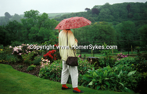 Lydeard St Lawrence, Somerset. 1990s<br /> In a splash of red amongst the wet evergreen English countryside a garden lover admires one mans toil and the Somerset countryside at the Broad Oak garden open day.