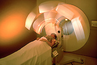 A female medical patient receives an MRI test - abstract view of machinery.