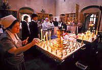 A celebrant (woman) lights candles during a memorial service in Kazan Cathedral, a Russian Orthodox church. Moscow, Russia central city.