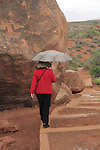 Asian woman walking with umbrella in Arches National Park, Moab, Utah, USA. .  John offers private photo tours in Arches National Park and throughout Utah and Colorado. Year-round.