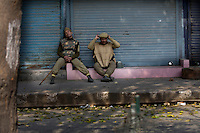 Bored paramilitary police during a curfew imposed to stop separists gather for a political demonstration in Srinagar, Kashmir, India. © Fredrik Naumann/Felix Features