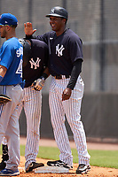 FCL Yankees manager Julio Borbon congratulates Alex Guerrero (63) during a game against the FCL Blue Jays on June 29, 2021 at the Yankees Minor League Complex in Tampa, Florida.  (Mike Janes/Four Seam Images)