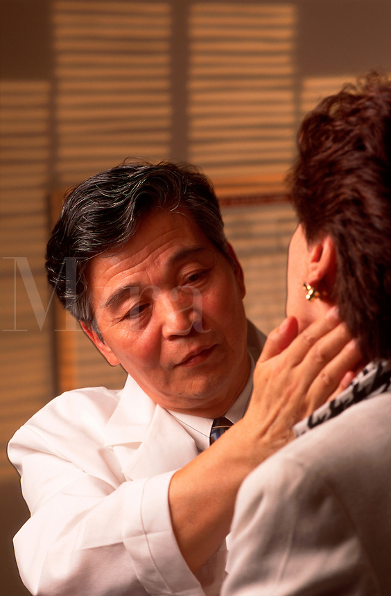 A male practitioner of traditional Chinese medicine (TCR) examines a female patient.