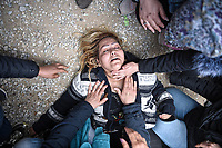 Pictured: A female migrant collapses on the ground in Diavata, Greece. Friday 05 April 2019<br /> Re: Clashes between migrants and riot police have broken out at the former Anagnostopoulos army camp, after rumours started spreading that the borders had re-opened, in Diavata near Thessaloniki, Greece