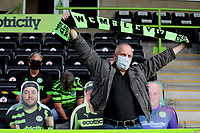 A forest green rovers fan holds his scarf aloft inside the stadium as forest green rovers take part in a pilot for fans returning to football during the Sky Bet League 2 match between Forest Green Rovers and Bradford City at The New Lawn, Nailsworth, England on 19 September 2020. Photo by Thomas Gadd.