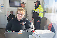 Volunteer load coordinator, Brittany Hanson does her magic at her radio and computer station inside the ACE fuels hut at the Willow, Alaska airport during the Food Flyout on Saturday, February 20, 2016.  Iditarod 2016