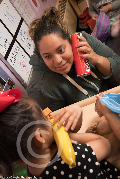 Education Preschool 2-3 year olds Head Start toddler program female teacher pretend play with girl both talking on telephones (substitution of toy banana and can for phones)