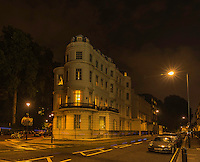 Night Scenic, street scene of a cobblestone street not far from Paddington Station, and Sussex Gardens in London England.<br /> The overhead streetlights cast a warm glow of shimmering highlights onto the cobblestones of the street.