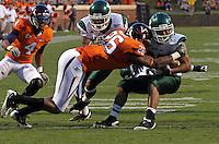 Oct 23, 2010; Charlottesville, VA, USA;  Virginia Cavaliers linebacker Ausar Walcott (26) tackles Eastern Michigan Eagles running back Javonti Greene (32) during the game at Scott Stadium.  Virginia won 48-21. Mandatory Credit: Andrew Shurtleff