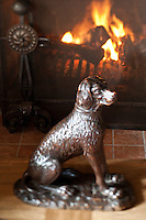 A carved wooden statue of a dog in front of the fireplace