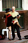 A elderly male tourist poses for a photograph with a street artist dancers San Telmo district Plaza Dorrego Buenos Aires 20002 2000s