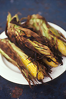 Corn in charred husks on a plate<br />