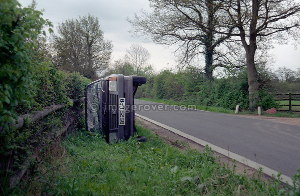 Car laying on its side after accident on small country road, Cranleigh, Surrey, UK. --- No releases available. Automotive trademarks are the property of the trademark holder, authorization may be needed for some uses.