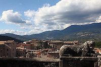 Alatri: A view of a part of the historical center from the garden at the top of the citadel's hill. There are the remains of a sculpted lion in foreground and mountains in the distance. It was a sunny day, amd the sky was partially clouded.