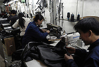 Workers sew jacket at a leather factory in Beijing, China..11-MAR-04