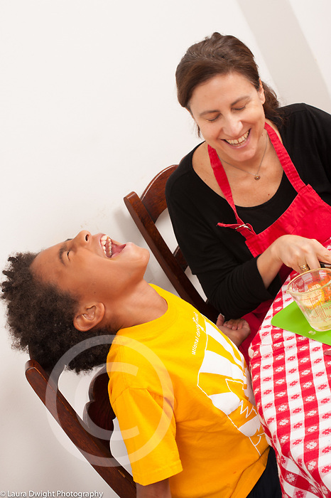 8 year old boy at home with mother in kitchen laughing with her as they prepare vegetables for salad