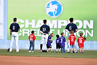 Asheville Tourists left fielder Vince Fernandez (8), center fielder Manny Melendez (19) and right fielder Willie Abreu (6) with fans during National Anthem before a game against the Greensboro Grasshoppers at McCormick Field on April 28, 2017 in Asheville, North Carolina. The Grasshoppers defeated the Tourists 7-4. (Tony Farlow/Four Seam Images)