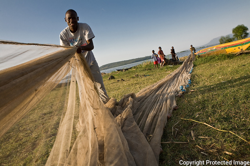 Dennis Okinyi Oluoch a secondary student and former fisherman helping his friends prepare for a night of fishing.