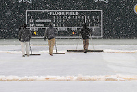 Members of the Fluor Field grounds crew clear snow from the playing field after a game between the Furman Paladins and Northwestern Wildcats was stopped after five innings due to heavy snow on Saturday, February 16, 2013, in Greenville, South Carolina. After a 90-minute delay the game was cancelled. (Tom Priddy/Four Seam Images)