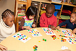 Education preschool 3-4 year olds group activity boys and girls sitting at table playing body parts bingo game using colored counters horizontal