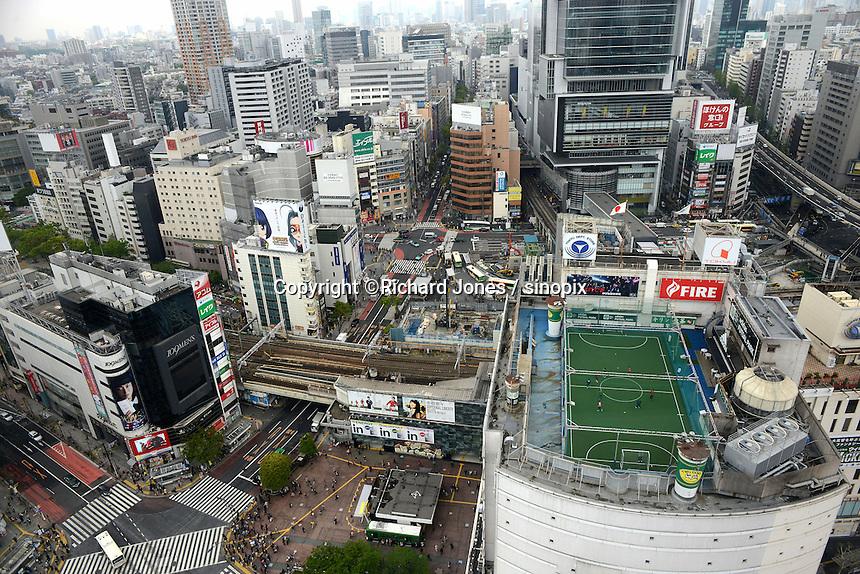 Boys play foot ball on a skyscraper football pitch, Shibuya city from above, Shibuya, Tokyo.<br /> April-2010