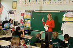 Education Elementary school Grade 2 female teacher talking to class green blackboard behind her student teacher sitting on side horizontal