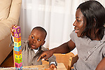 2 year old toddler boy building tall stack of blocks as mother looks on and encourages him