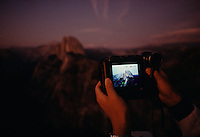 Japanese tourists visiting Yosemite National Park at dusk,  try out a new video camera at Half Dome.