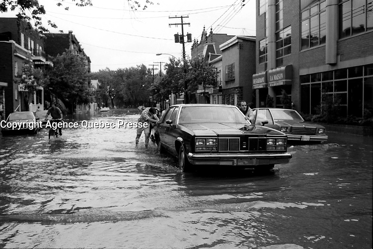 Innondation du 14 juillet 1987.<br /> <br /> <br /> <br /> <br /> <br /> <br />  July 14, 1987  File Photo -  A fierce flash flood struck Montreal on July 14, 1987. As severe thunder storms and intense rainfall deluged the city, drainage systems were unable to accommodate the massive runoff. Major expressways were flooded with over 3 metres of water, requiring that people be rescued from their cars. The public transportation system was in chaos. Backed up sewers flooded houses and businesses, and thousands were without electricity.<br /> <br /> Montreal had been experiencing a heat wave when on July 14, thunder storms dumped in excess of 100 millimetres (mm) of rain. A recording station at McGill University measured 86 mm of rain in a one-hour period. Rainfalls measuring 100 mm at Parc Lafontaine, 92 mm at the Botanical Gardens, and 99 mm at Dorval Airport were also recorded. Accompanying the thunderstorms were tremendous winds that uprooted large trees and toppled hydro lines.