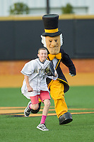 A young fan runs away from the Wake Forest Demon Deacon mascot after having grabbed a bag of goodies from him between innings of the game against the North Carolina State Wolfpack at Wake Forest Baseball Park on March 16, 2013 in Winston-Salem, North Carolina.  The Demon Deacons defeated the Wolfpack 13-4.  (Brian Westerholt/Four Seam Images)
