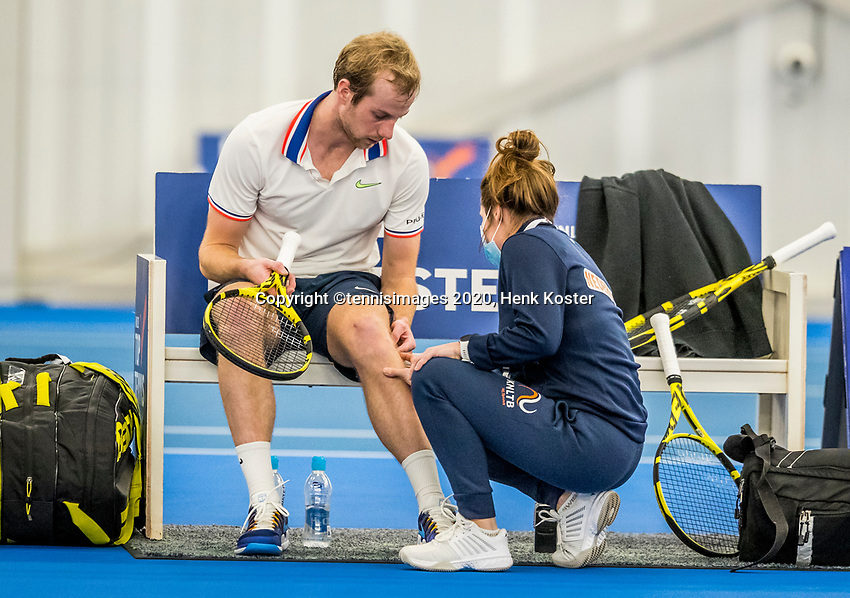 Amstelveen, Netherlands, 20  December, 2020, National Tennis Center, NTC, NK Indoor, National  Indoor Tennis Championships, Men's  Single Final   :  Botic van de Zandschulp (NED) is being treatet for a knie injury by fysio  Lisette Hagen, later he gives up the match<br /> Photo: Henk Koster/tennisimages.com