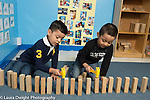 Education Preschool 4 year olds two boys hammering with toy hammers after building row of blocks