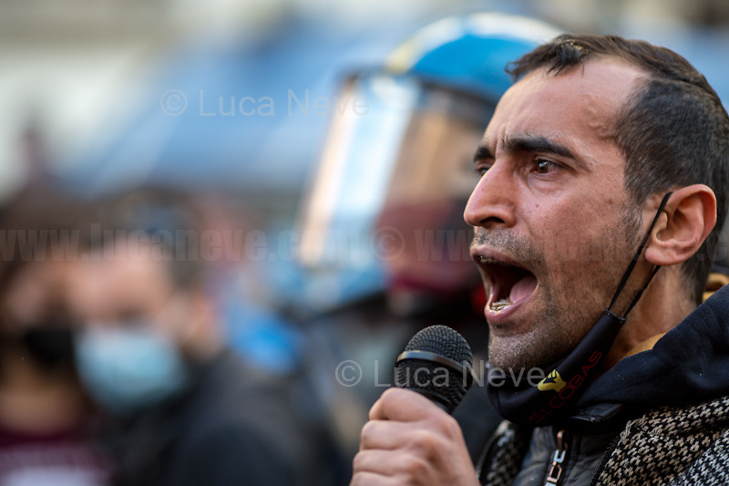 Logistic Workers Representative. <br /> <br /> Rome, Italy. 18th Feb 2021. Today, the Trade Union Si Cobas, Potere Al Popolo Party, Rifondazione Comunista Party and other organizations of the non-parliamentarian Left held a rally (1.) in Piazza San Silvestro to protest against the new Italian Government led by the former President of the European Central Bank, BCE, Professor Mario Draghi (2. 3.). From the organisers Facebook event page: «[…] We call to mobilize male and female workers, the unemployed, the precarious, the students, the popular classes and all the associations and people who struggle, who do not want to stand by while a government that is directed expression of a united bosses front is ready to strike us with anti-people policies. It is time to join the fight against the government of banks and bosses: we will not pay for this crisis! […]». The demo ended peacefully, even though there were moments of tension between protesters and full riot gears police officers due to demonstrators aimed to march to the Parliament.<br /> <br /> Footnotes & Links:<br /> 1. https://www.facebook.com/events/4966336456769715<br /> 2. 13.02.2021 - Mario Draghi's New Italian Government Swears At Quirinale Palace http://bit.do/fNPQ5<br /> 3. 17.02.2021 - Italian Prime Minister Mario Draghi Arrives at Italian Senate http://bit.do/fNPRc