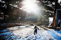 A young child, from a migrant family, plays in the snow where he lives in an old disused brick factory in a Bishkek suburb.