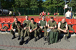 """Polish soldiers sit on the sidelines of a soccer match during a day off for cultural activities, which included sports games between the different participating armies in the NATO """"Saber Strike"""" military exercises, in Drawsko Pomorskie, Poland on June 13, 2015.  NATO is engaged in a multilateral training exercise """"Saber Strike,"""" the first time Poland has hosted such war games, involving the militaries of Canada, Denmark, Germany, Poland, and the United States."""