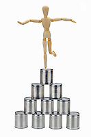 Mannequin balancing on top of tin cans pyramid (Licence this image exclusively with Getty: http://www.gettyimages.com/detail/102918625 )