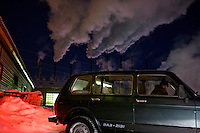 A man drives a car past a steaming water-heating plant in Naryan-Mar, capital of the resource-rich Nenets Autonomous Region in Arctic Russia. /Felix Features