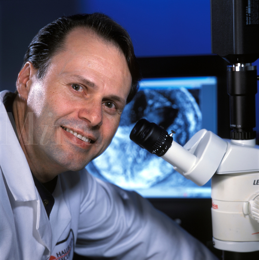 research technician with microscope