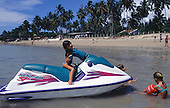 Itaparica Island, Bahia, Brazil. Children playing on a Jetski by the beach at Mar Grande.