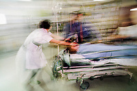 Doctor and nurses rushing a patient into an A&E emergency room